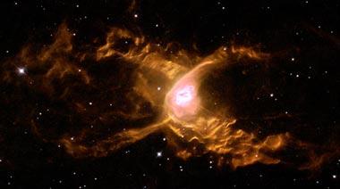 """Ein anderer Planetarer Nebel, der """"Rote Spinne"""" Nebel, wird von den stellaren Winden des Weißen Zwerges im Zentrum, wellenförmig verformt (Foto NASA und Hubble Heritage Team)"""